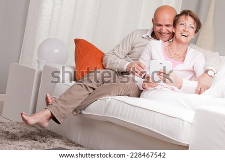 old woman and old men happy together because they love each other in a living room on a sofa - stock photo