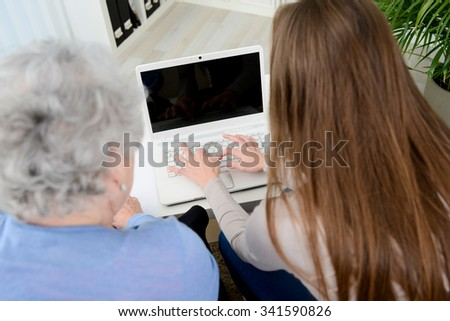 old woman at home with cheerful young girl spending time together with a laptop computer