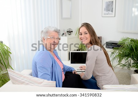 old woman at home with cheerful young girl spending time together with a laptop computer - stock photo