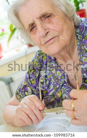 old woman can't read the book - stock photo