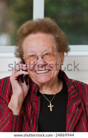 Old woman carries a telephone conversation with mobile phone - stock photo