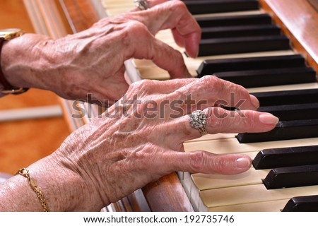 Old woman close up of hands  playing the piano  - stock photo