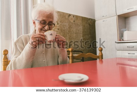 Old woman drinking a coffee sitting in the kitchen. old people and seniority concept - stock photo