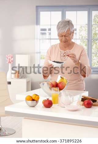 Old woman eating blueberry, many fruits on kitchen counter. - stock photo