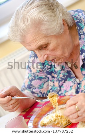 Old woman eating soup - stock photo