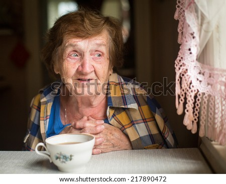 Old woman emotionally talking sitting near the window in his country house. - stock photo