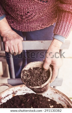 Old woman filling a pot with fresh soil. Symbol of spring and clean eating concept.