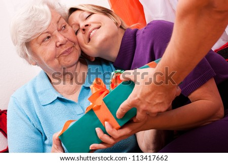 old woman gets a gift, young woman is happy about