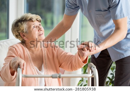 Old woman gets help with walking from a nurse