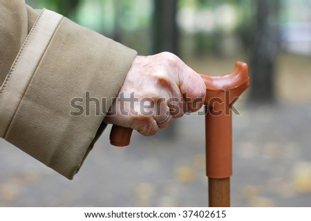 Old woman hand leans on walking stick - stock photo