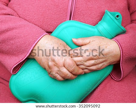 Old woman holding a water bottle to keep warm - stock photo