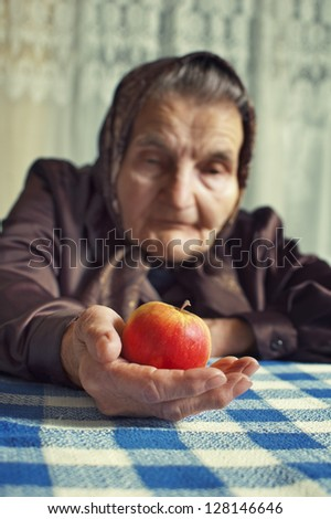 Old woman holding an apple. Selective focus on apple. - stock photo