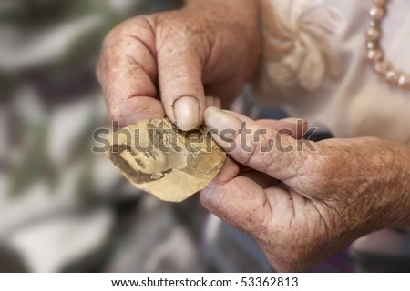 Old woman holding own photo in age of twenty. - stock photo