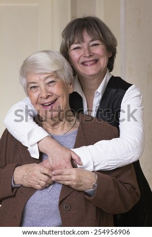 Old woman hugged by daughter