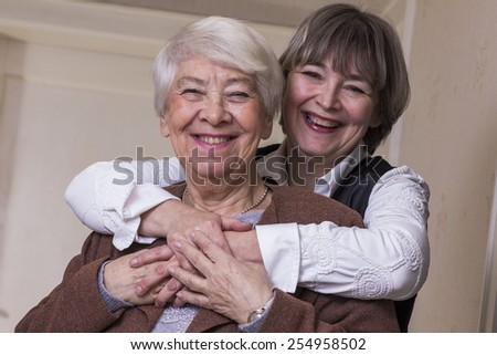 Old woman hugged by daughter - stock photo
