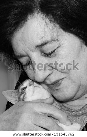 Old woman hugging little kitten.