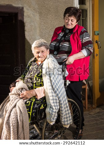Old woman in a wheelchair and her daughter near the house  - stock photo