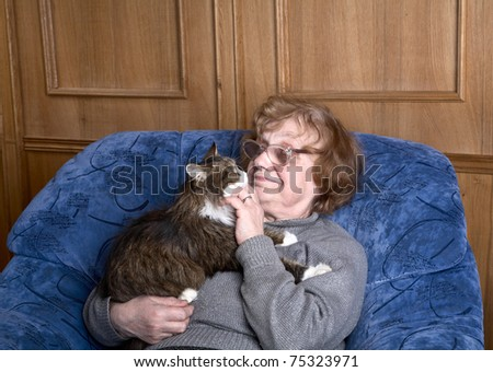 old woman in an armchair with a cat on hands - stock photo