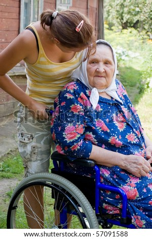 old woman in an invalid armchair - stock photo