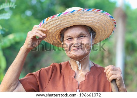 old woman in hat working in the garden. - stock photo
