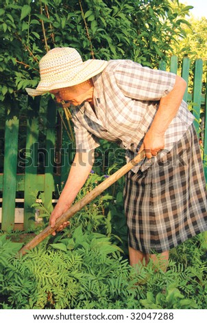 old woman in hat working in the garden - stock photo