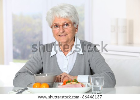Old woman in nursing home ready to have dinner - stock photo