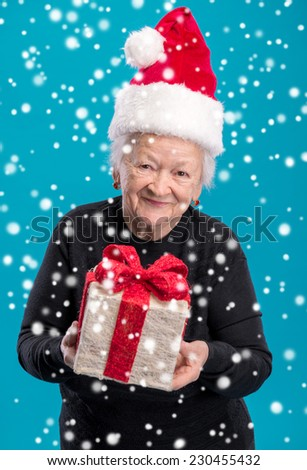 Old woman in santa hat with gift box. Christmas and holidays concept - stock photo