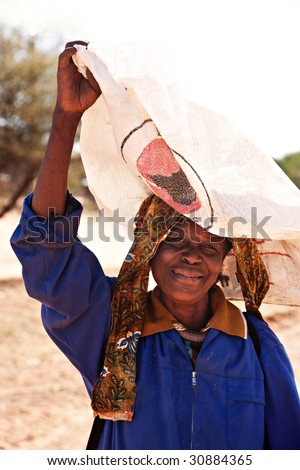 old woman in village near Zanzibar border post carry a raffia sac on the head - stock photo