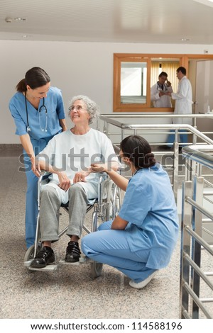 Old woman in wheelchair talking with nurses in hospital corridor - stock photo