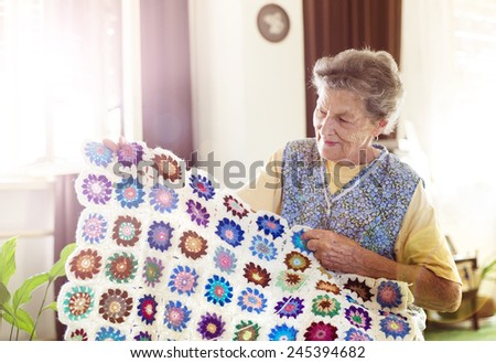 Old woman is knitting a blanket inside in her living room - stock photo
