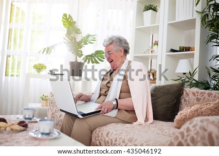 Old woman laughing and watching funny movie on her laptop  - stock photo