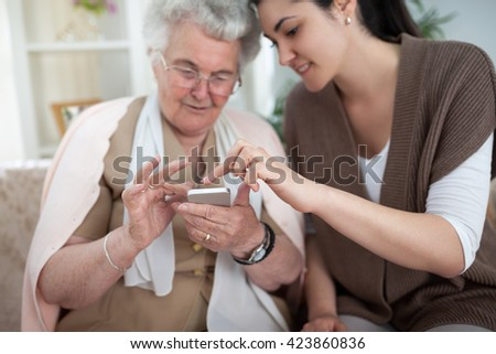 Old woman learning to use smartphone with a help of young woman - stock photo