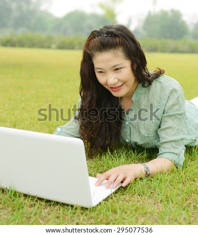 Old woman lie on the grass using laptops