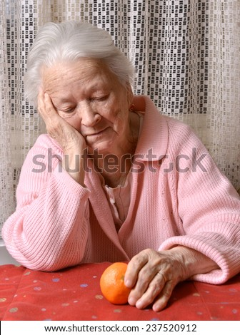Old woman looking at tangerine at home - stock photo