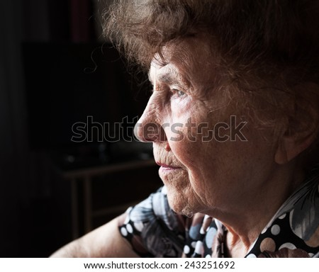 Old woman looking away. Elderly female at home - stock photo