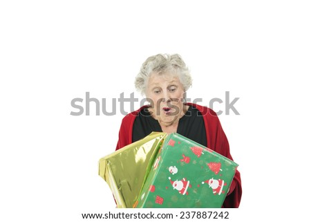 Old woman looking down at christmas presents against a white background - stock photo