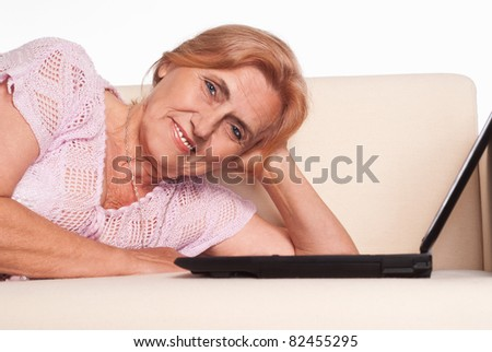 old woman lying on sofa with laptop