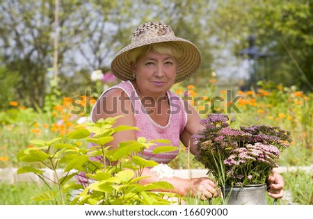 Old woman maintains a garden - stock photo