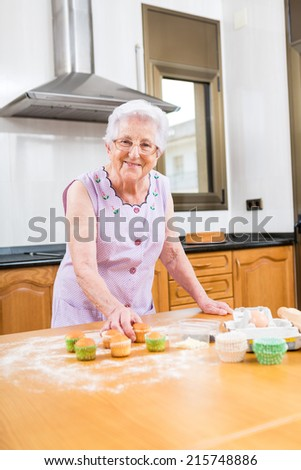 old woman making and decorating cupcakes stock photo