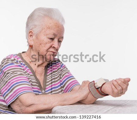 Old woman measures arterial pressure on a white background