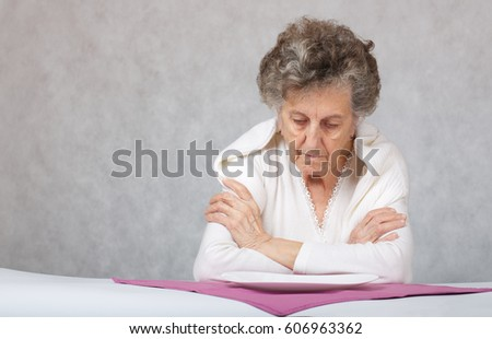 Old woman of 80 years old in front of an empty plate.