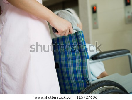old woman on a wheelchair with assistant - stock photo