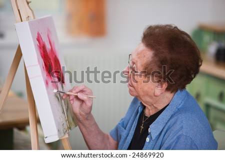 Old woman paints a picture - stock photo