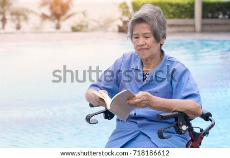Old woman patient sitting on wheelchair roller and reading a book, alone at swimming pool edge.