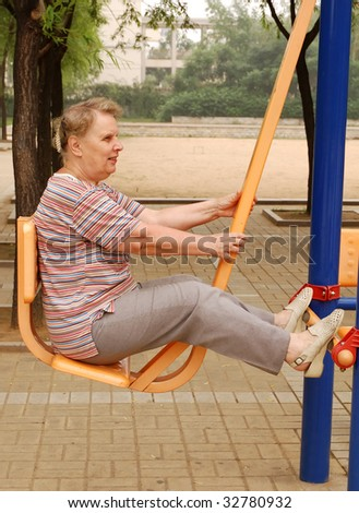 old woman practice on the gym apparatus - stock photo