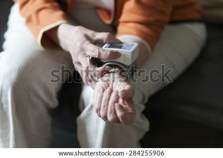 Old woman reading her blood pressure meter from the arm. - stock photo