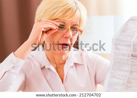 Old woman reading  medicament package insert at home with glasses - stock photo