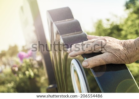 Old woman's hand on the grave of her husband.  - stock photo