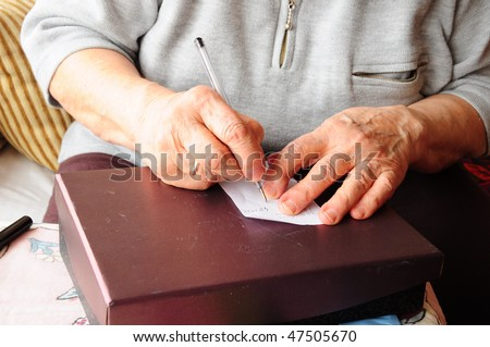 old woman's hands writing on a white paper - stock photo