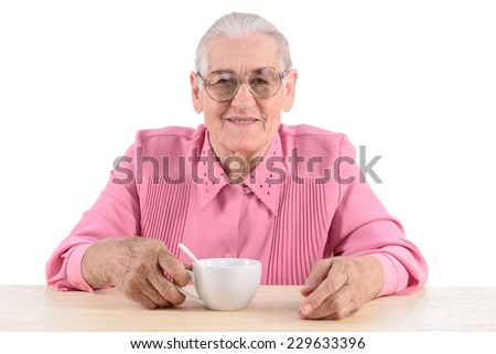 old woman sitting near table and holding a cup of tea. portrait isolated on white background - stock photo
